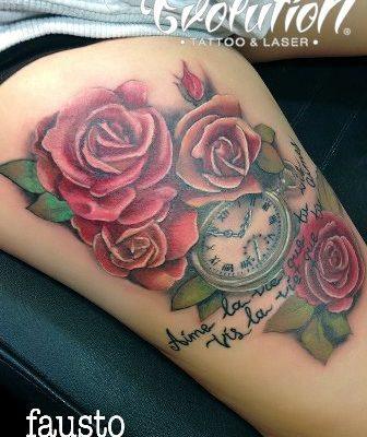 tatuaje rosas rojas y reloj junto a frase evolution tattoo